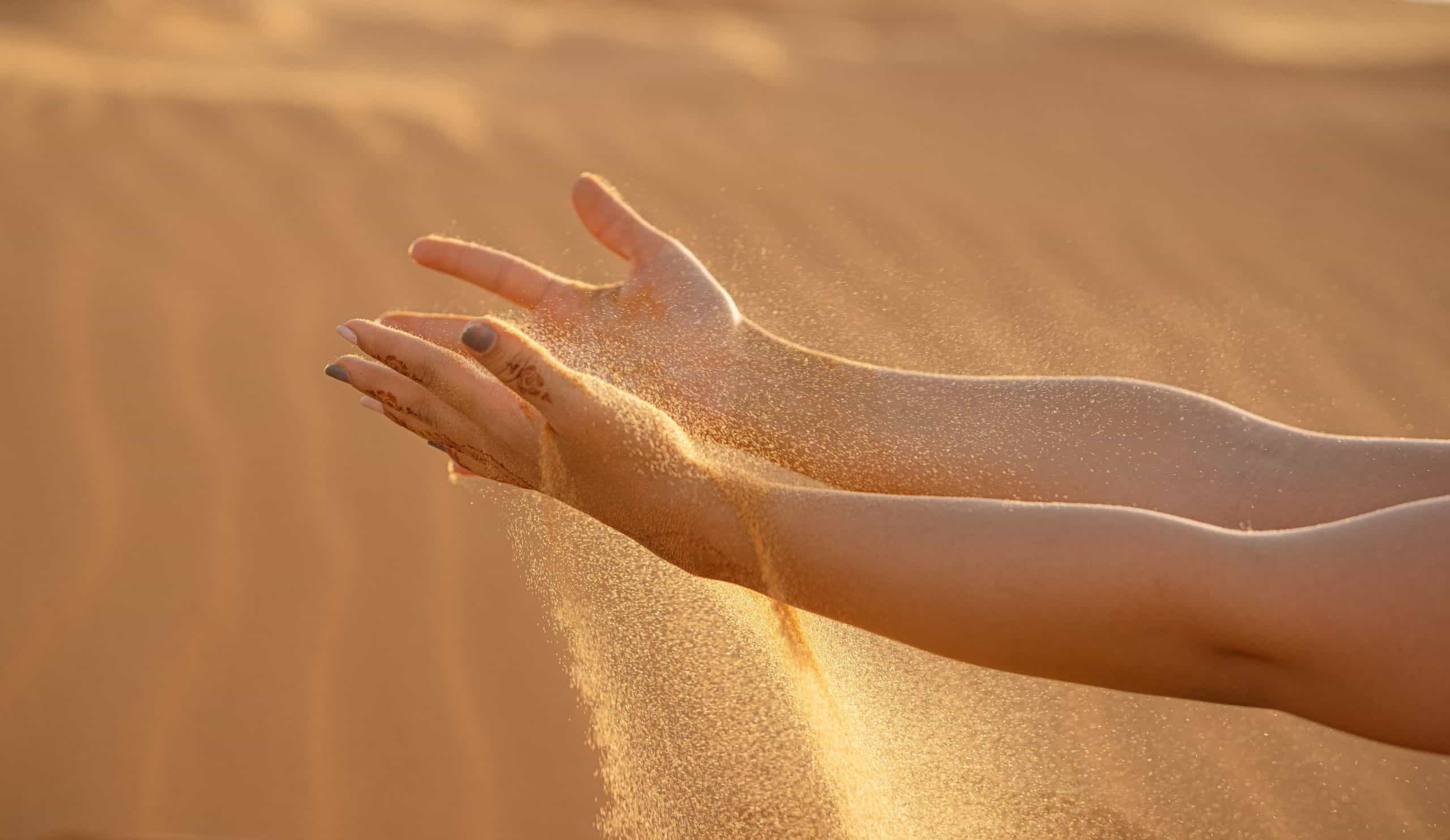 A close up of feet in the sand
